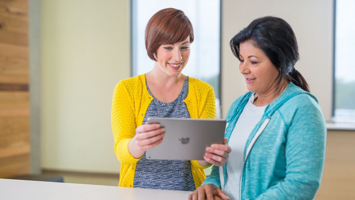 Five-Considerations-for-Implementing-a-Care-Management-Strategy_same 2 women above talking one holding with tablet