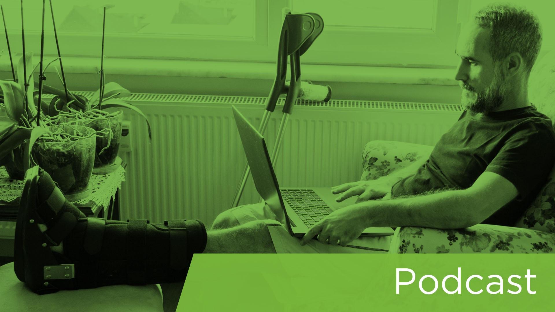 Man with injured leg using laptop