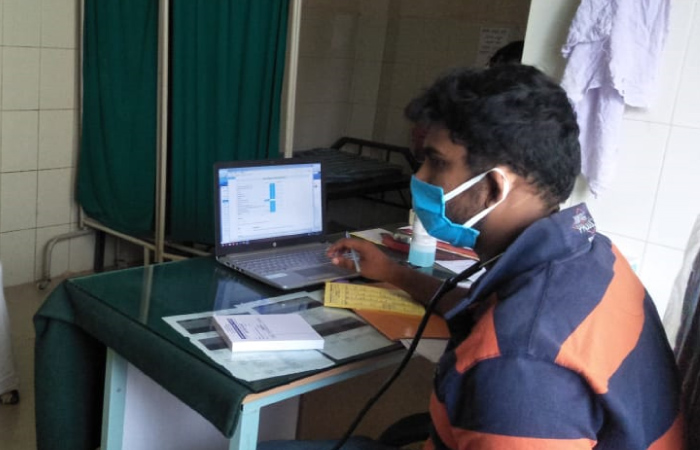 Karuna Trust staff use a laptop while working with patients image_staff member uses computer