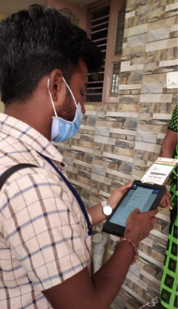 A healthcare worker goes door to door to speak with people about COVID-19 and to learn if they may be positive with the virus image_healthcare worker uses tablet