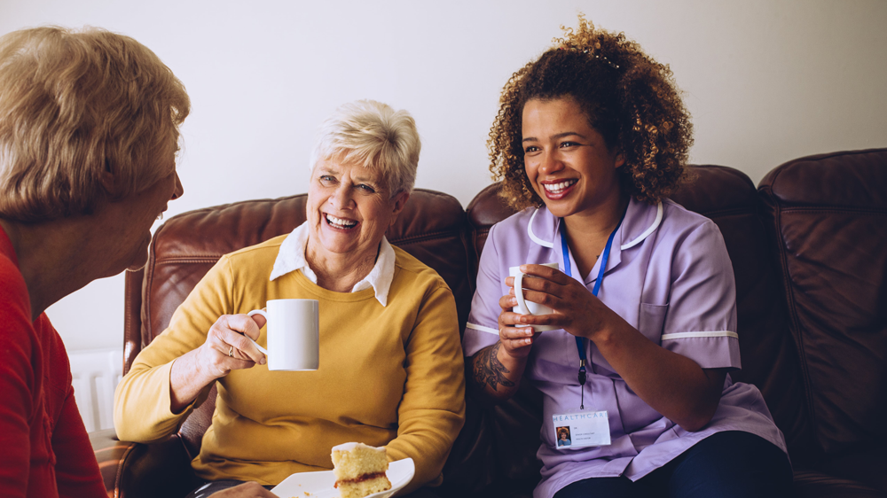 Caregiver sharing tea with patients
