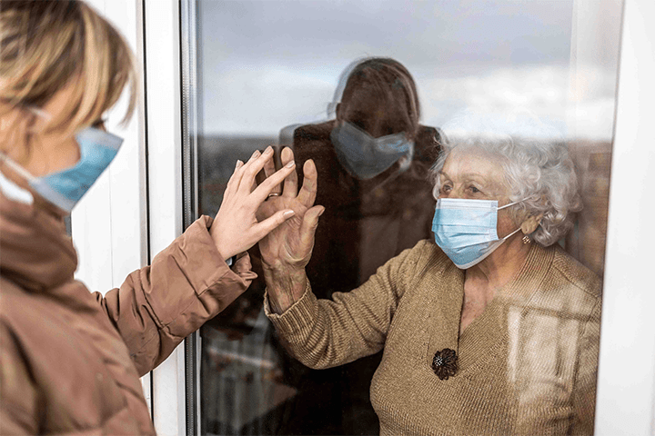 Woman visiting elderly lady during COVID-19 pandemic.