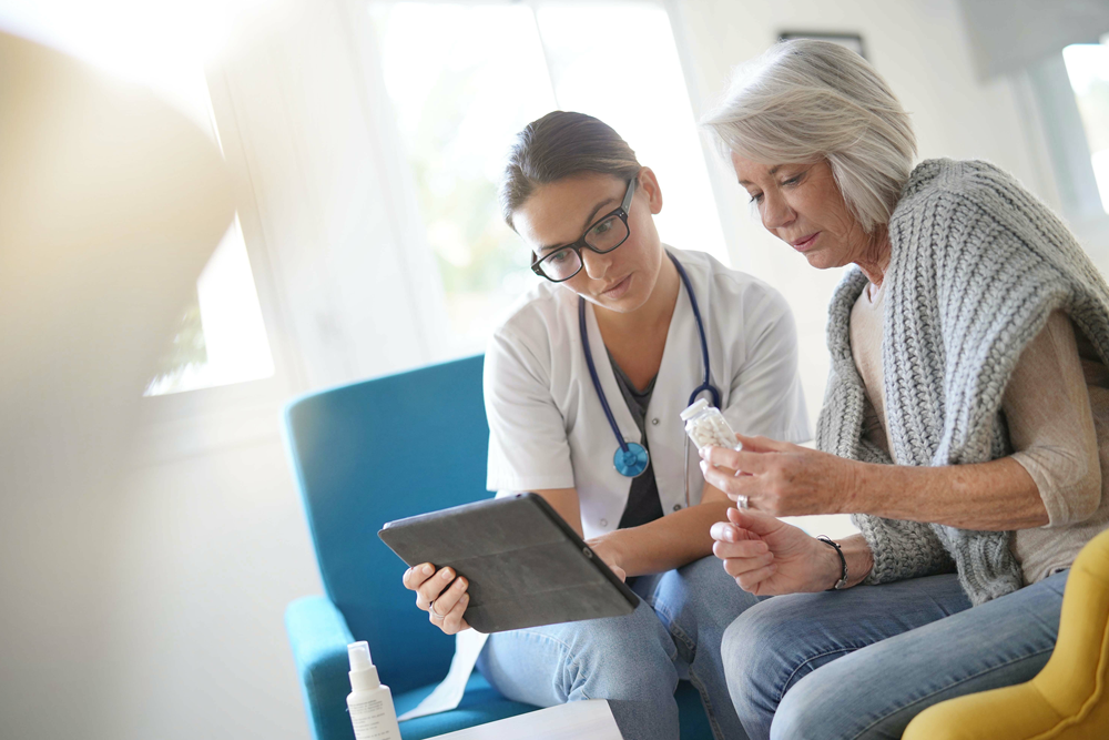 Doctor and patient sitting together, looking at tablet device